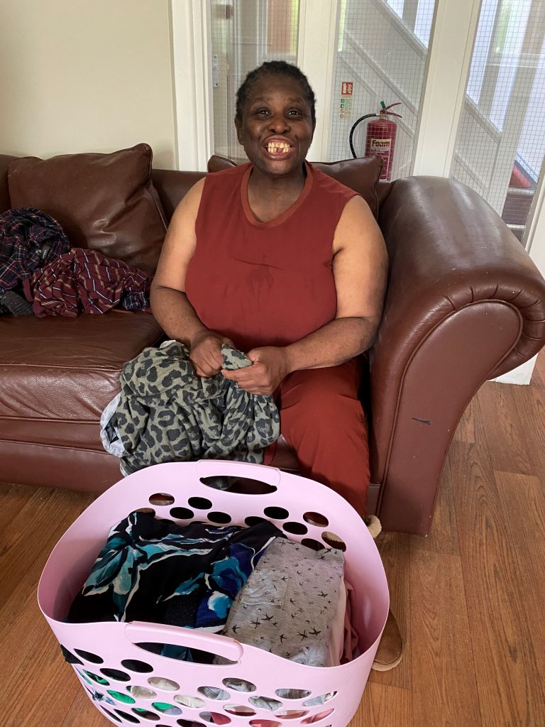 Person we support smiling with a laundry basket