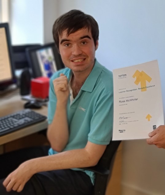 Ross smiling with his achievements certificate