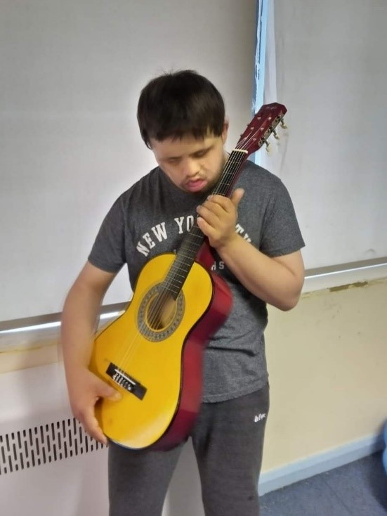 Jamie holding his guitar